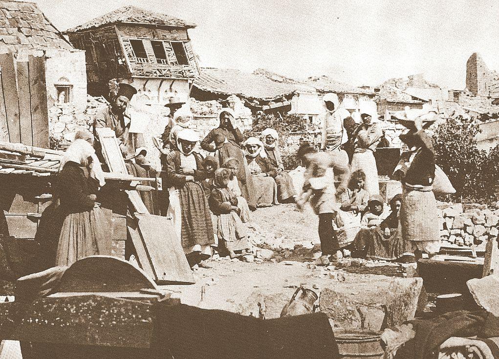 1881. Νενητούσαινες με τα παιδιά τους και τον παπά του χωριού μπροστά στα μισογκρεμισμένα σπίτια τους. Φωτογραφία των αδελφών Castania.