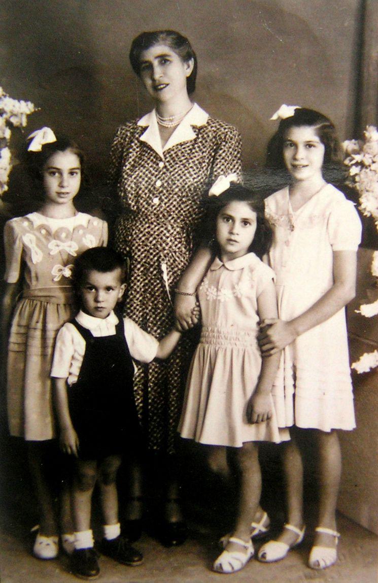 Βροντάδος, 1950. Ελαφρά γερμένο το κεφάλι της μητέρας -υπόνοια της θηλυκότητας που αναλώθηκε για να υπηρετεί την πάστρα και τη νοικοκυροσύνη- και το χέρι της χαλαρό στην τρυφερή συνάντησή του με το χεράκι του μοναχογιού. Οικογενειακή φωτογραφία της Μαρίας Pυμική, το γένος Χούλη, με τα παιδιά της. Αποδέκτης ο σύζυγος-ναυτικός και μετέπειτα προσωρινός μετανάστης στην Αμερική.